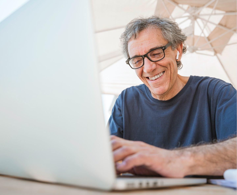 older man working on laptop